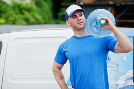Delivery man in front cargo van delivering bottles of water.