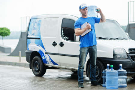 Delivery man with clipboard in front cargo van delivering bottles of water.