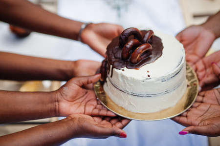 Group of african american girls celebrating birthday party outdoor. Black hands with cake.