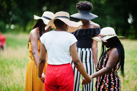 Group of four gorgeous african american womans wear summer hat holding hands and praying at green grass in park. Stok Fotoğraf