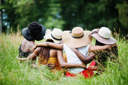 Back view of group four gorgeous african american womans wear summer hat sitting at green grass in park. Stok Fotoğraf