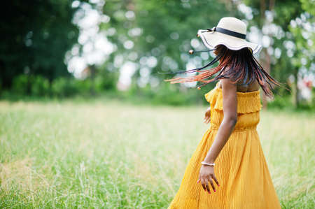 Portrait of gorgeous african american woman 20s in wear in yellow dress and summer hat posing at green grass in park.