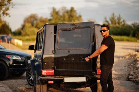 Asian man wear on all black posed near suv car, open rear door.