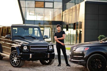 Asian man wear on all black posed near suv car.