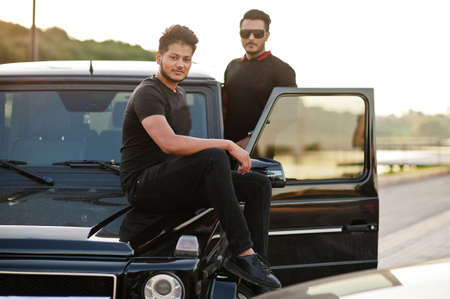 Two asian brothers man wear on all black posed near suv car.