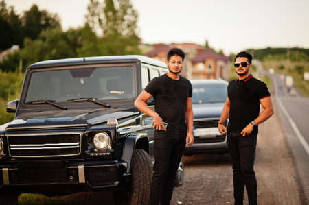 Two asian brothers man wear on all black posed near suv cars.