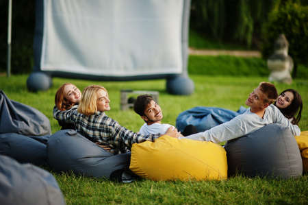 Young multi ethnic group of people watching movie at poof in open air cinema. Imagens