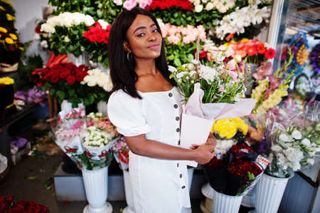 Beautiful african american girl in tender white dress with bouquet flowers in hands standing against floral background in flower shop.Black female florist.