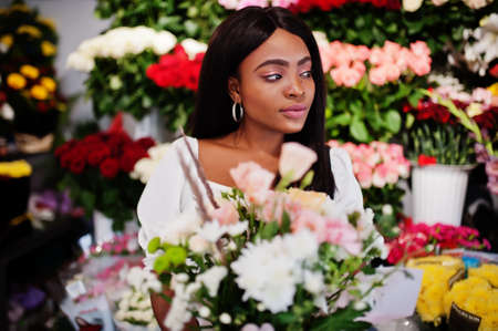 Beautiful african american girl in tender white dress with bouquet flowers in hands standing against floral background in flower shop.Black female florist. Stockfoto