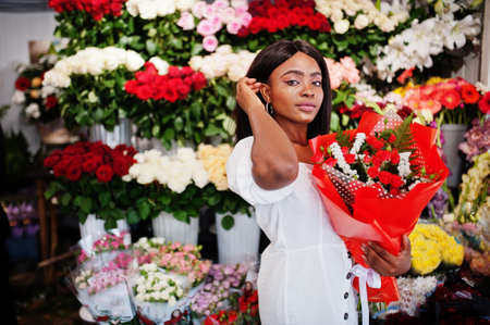 Beautiful african american girl in tender white dress with bouquet flowers in hands standing against floral background in flower shop.Black female florist. Stock Photo