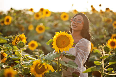 Pretty young black woman wear summer dress pose in a sunflower field.