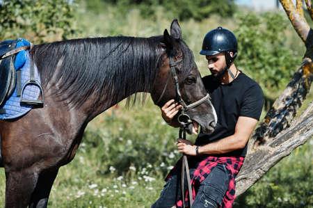 Arab tall beard man wear in black helmet with arabian horse.