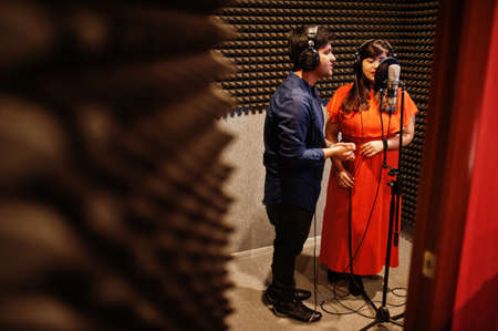 Young asian duet singers with microphone recording song in record music studio.