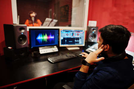 Young asian singer with microphone recording song in record music studio with sound producer.