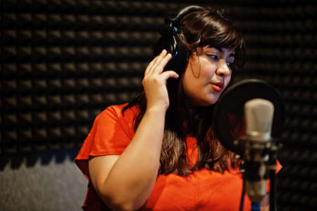 Young asian singer with microphone recording song in record music studio. Фото со стока