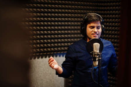 Young asian singer man with microphone recording song in record music studio.