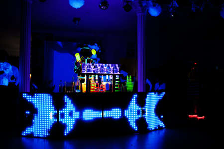 Professional barman and led light show. Silhouette of modern bartender shaking drink at night cocktail bar. Stock Photo