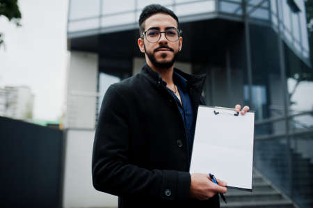 Middle eastern man wear black coat, eyeglasses, hold white empty clipboard. Imagens