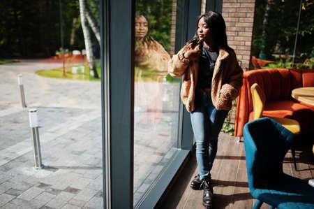 Fashionable african american woman wear jacket standing near window. Imagens