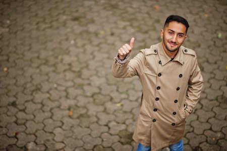 Stylish kuwaiti man at trench coat show thumb up.