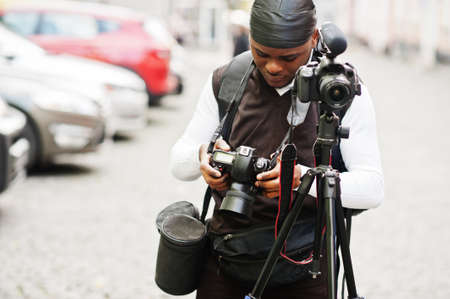Young professional african american videographer holding professional camera with tripod pro equipment. Afro cameraman wearing black duraq making a videos.