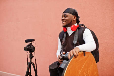 Young professional african american videographer holding professional camera with pro equipment. Afro cameraman wearing black duraq making a videos.