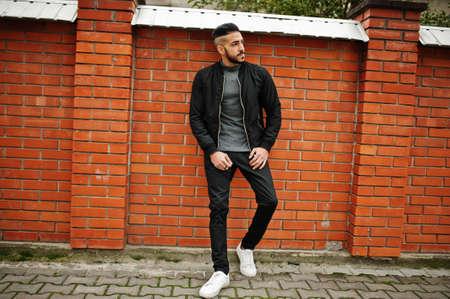 Portrait of stylish arab beard man wear gray turtleneck and black jaket. Arabian model guy against brick wall. Reklamní fotografie