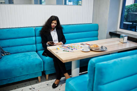 Indian artist woman wear formal paint picture and listening hindu music from earphones, while sitting at cafe.