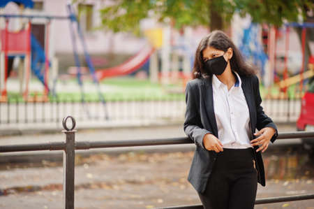 Gorgeous indian woman wear formal and black face mask, posing at street during covid pandemia. Archivio Fotografico
