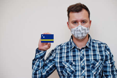 Man in checkered shirt show Curaçao flag card in hand, wear protect mask isolated on white background. American countries Coronavirus concept.