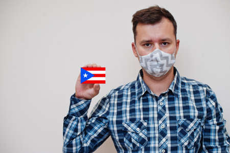 Man in checkered shirt show Puerto Rico flag card in hand, wear protect mask isolated on white background. American countries Coronavirus concept.