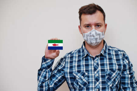 Man in checkered shirt show Federal Dependencies of Venezuela flag card in hand, wear protect mask isolated on white background. American countries Coronavirus concept.