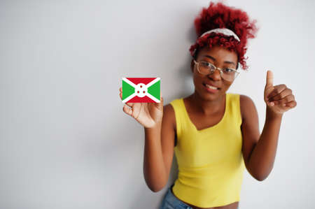 African woman with afro hair, wear yellow singlet and eyeglasses, hold Burundi flag isolated on white background, show thumb up.