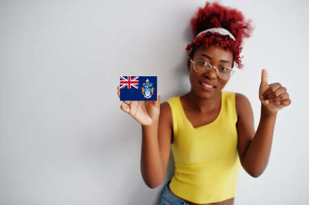African woman with afro hair, wear yellow singlet and eyeglasses, hold Tristan da Cunha flag isolated on white background, show thumb up.