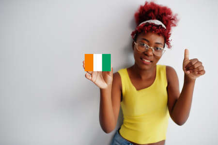 African woman with afro hair, wear yellow singlet and eyeglasses, hold Ivory Coast flag isolated on white background, show thumb up.
