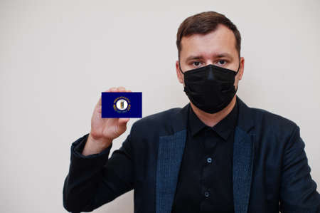 Man wear black formal and protect face mask, hold Kentucky flag card isolated on white background. USA coronavirus Covid country concept.