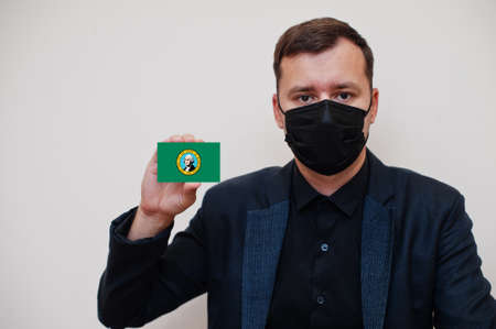 Man wear black formal and protect face mask, hold Washington flag card isolated on white background. USA coronavirus Covid country concept.