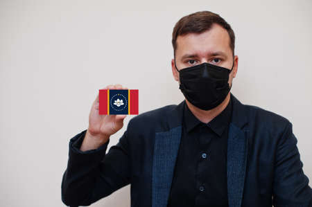 Man wear black formal and protect face mask, hold Mississippi flag card isolated on white background. USA coronavirus Covid country concept. 版權商用圖片