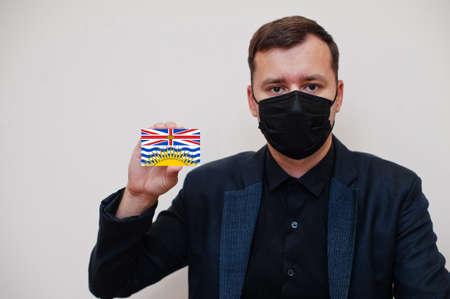Man wear black formal and protect face mask, hold British Columbia flag card isolated on white background. Canada provinces coronavirus Covid country concept. 版權商用圖片
