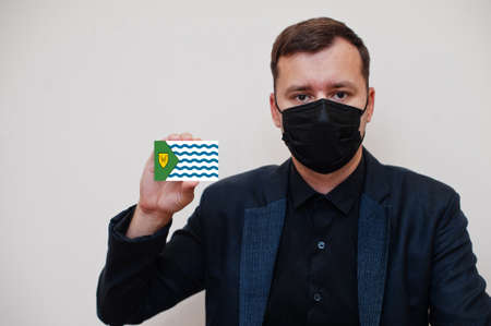 Man wear black formal and protect face mask, hold Vancouver flag card isolated on white background. Canada cities coronavirus Covid concept. 版權商用圖片