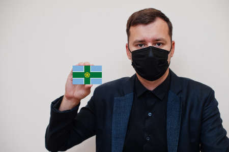 Man wear black formal and protect face mask, hold Derbyshire flag card isolated on white background. United Kingdom counties of England coronavirus Covid concept.