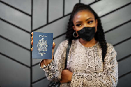 African american woman wearing black face mask show Canada passport in hand. Coronavirus in America country, border closure and quarantine, virus outbreak concept.