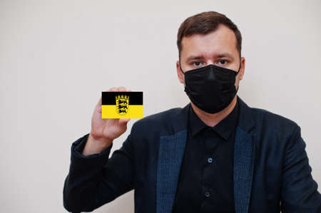 German man wear black formal and protect face mask, hold Baden-Wurttemberg flag card isolated on white background. Germany states coronavirus Covid concept.