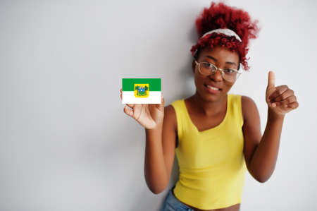 Brazilian woman with afro hair hold Rio Grande do Norte flag isolated on white background, show thumb up. States of Brazil concept.
