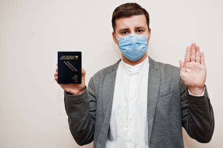 European man in formal wear and face mask, show Bosnia and Herzegovina passport with stop sign hand. Coronavirus lockdown in Europe country concept.