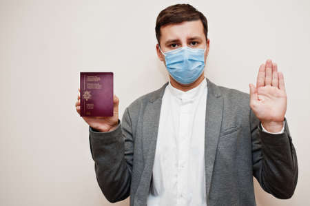 European man in formal wear and face mask, show Belgium passport with stop sign hand. Coronavirus lockdown in Europe country concept.