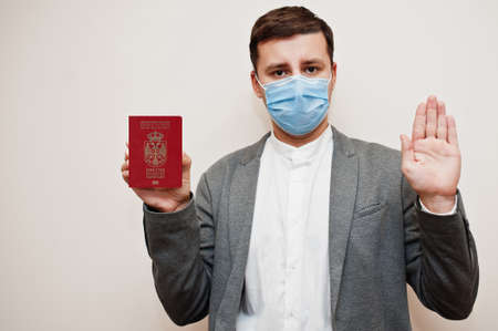 European man in formal wear and face mask, show Serbia passport with stop sign hand. Coronavirus lockdown in Europe country concept.