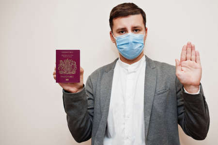 European man in formal wear and face mask, show Isle of Man passport with stop sign hand. Coronavirus lockdown in Europe country concept.
