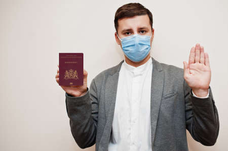 European man in formal wear and face mask, show Netherlands passport with stop sign hand. Coronavirus lockdown in Europe country concept.