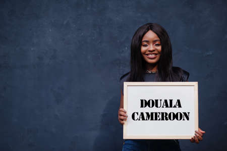 African woman hold white board with Douala Cameroon inscription. Most populous city in Africa concept. Imagens